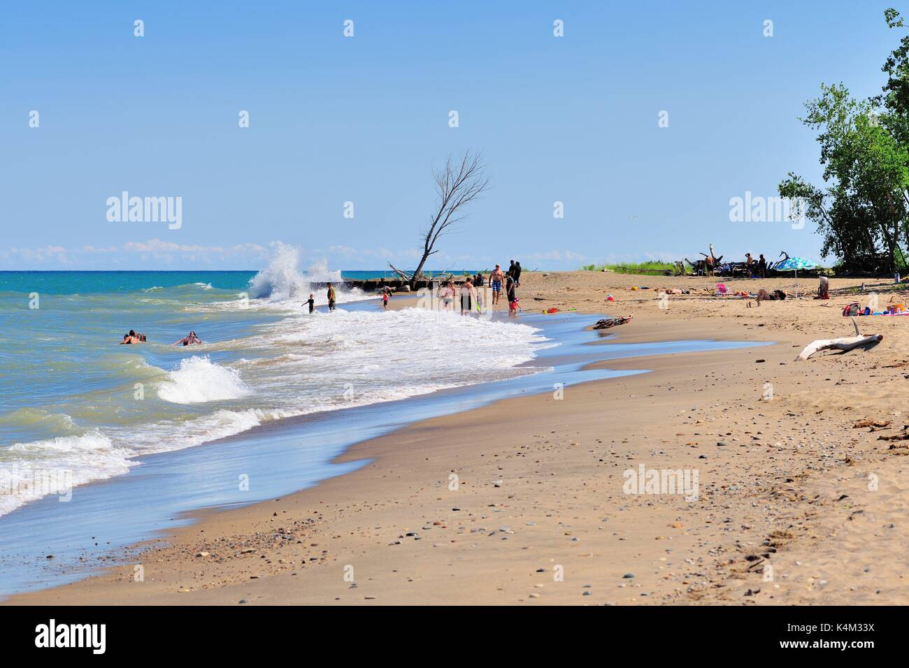 A few people play or walk in the pounding surf or relax in the remote sand at North Beach in the Illinois Beach State Park. Winthrop Harbor, Illinois, - Stock Image