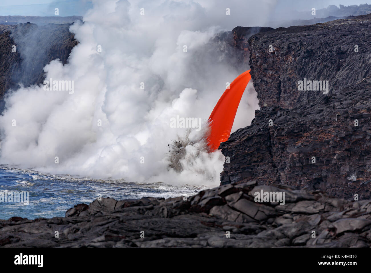 Closeup view of the red molten lava of an active volcano from a mountaintop in Hawaii's National Park flowing like a fire hose the massive cloud of st - Stock Image