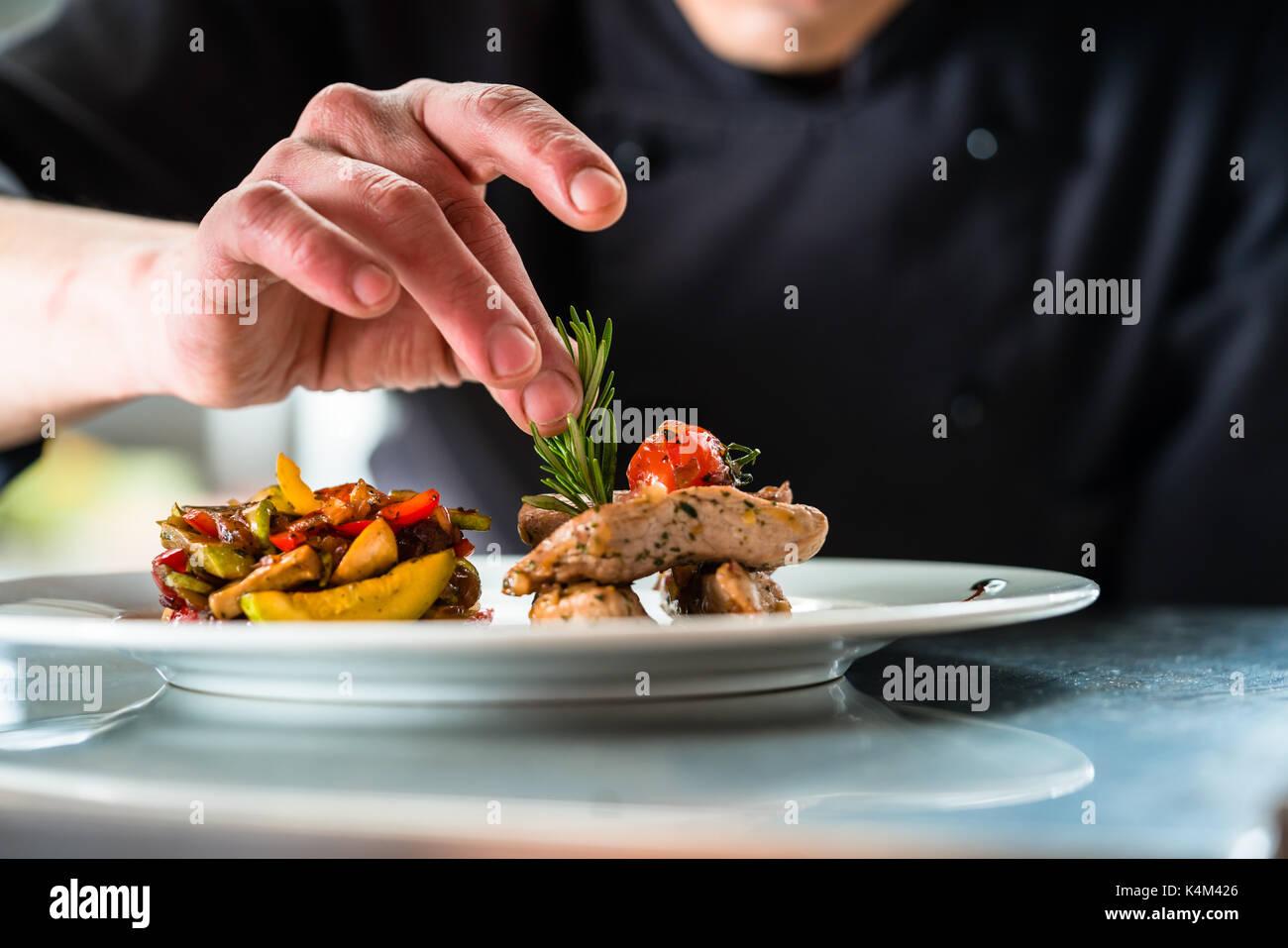 Chef finishing and garnishing food he prepared - Stock Image