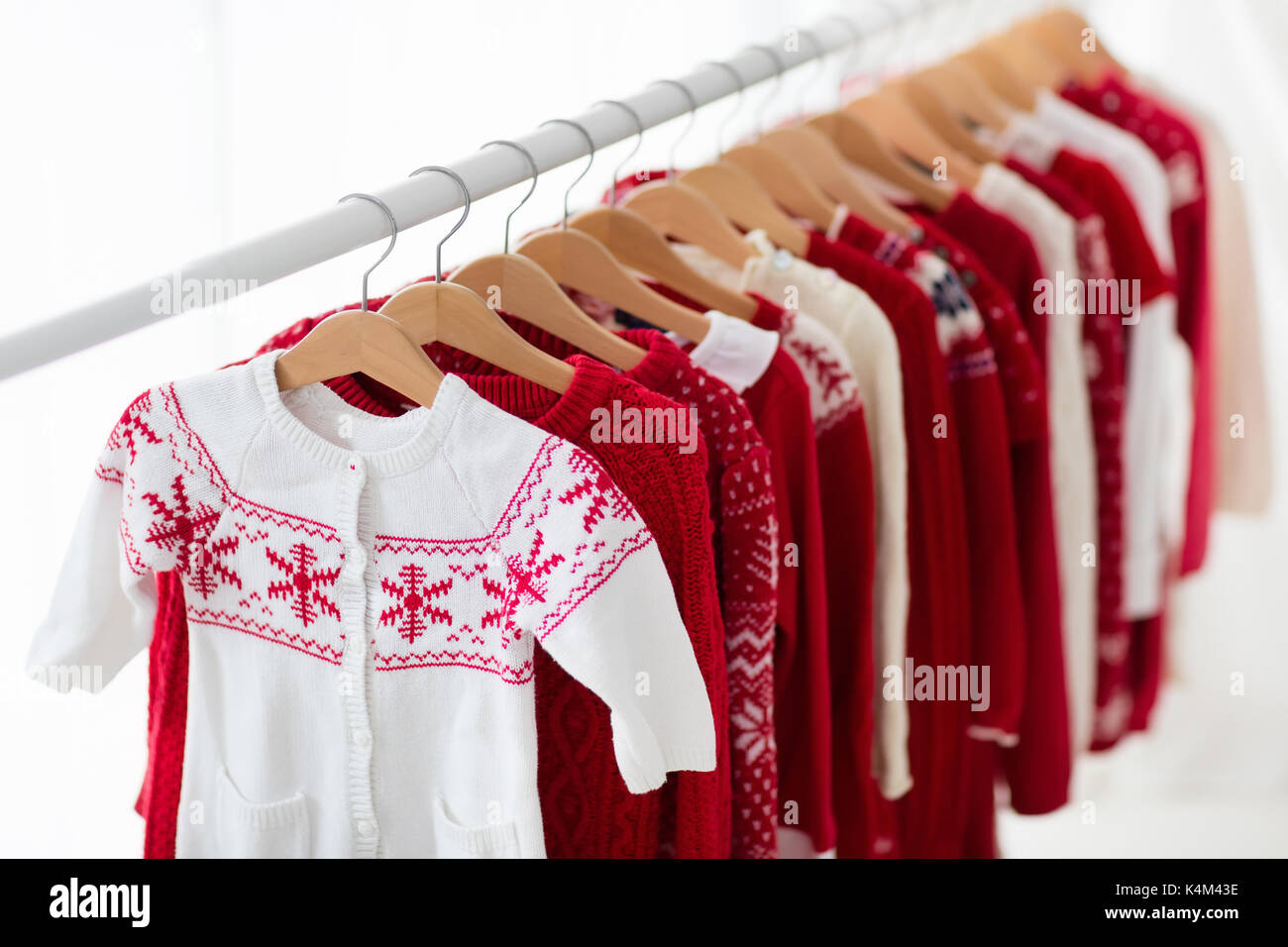 Clothes rack with red Christmas knit wear. Wardrobe with knitted ...