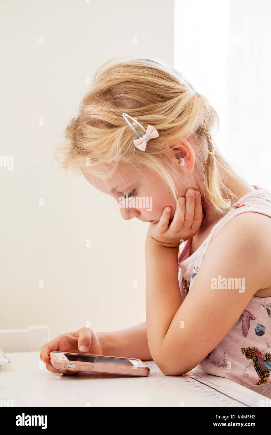 Little girl playing with smart phone - Stock Image