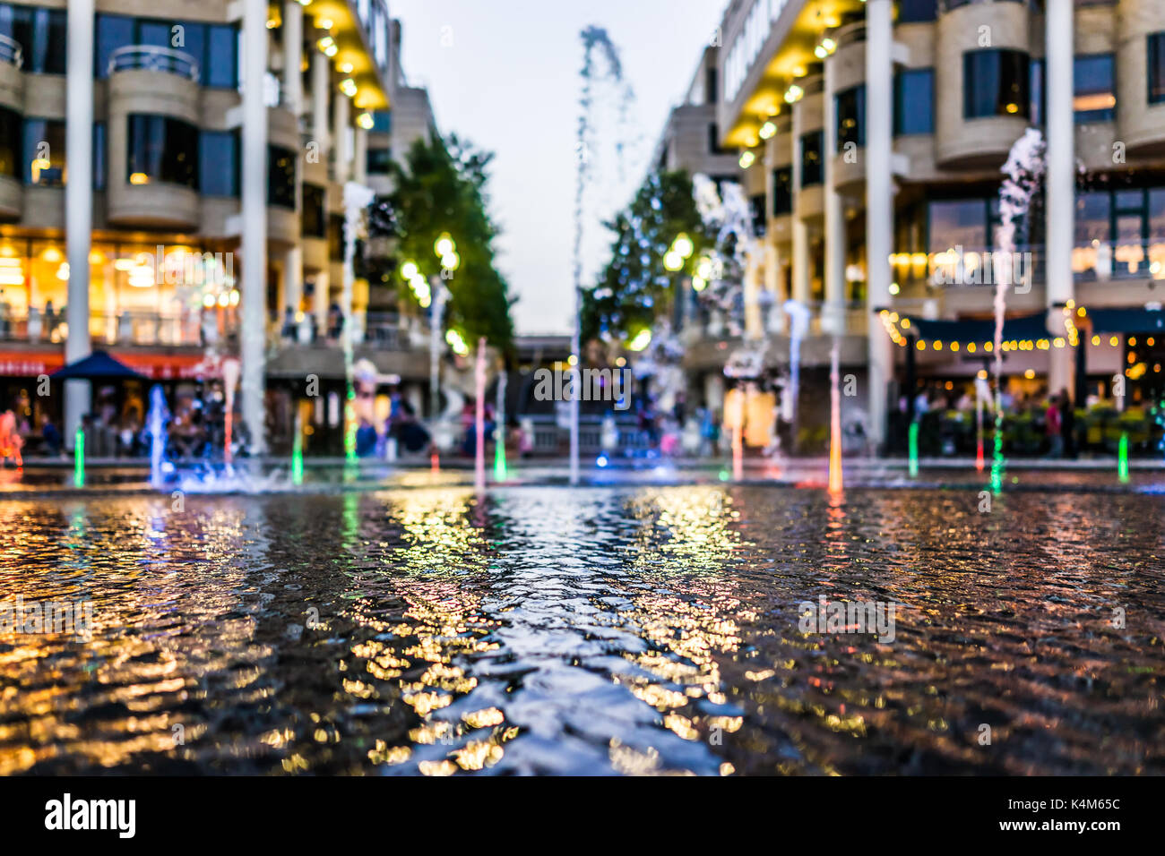 Closeup of colorful fountain at night in Georgetown Harbor with restaurants - Stock Image