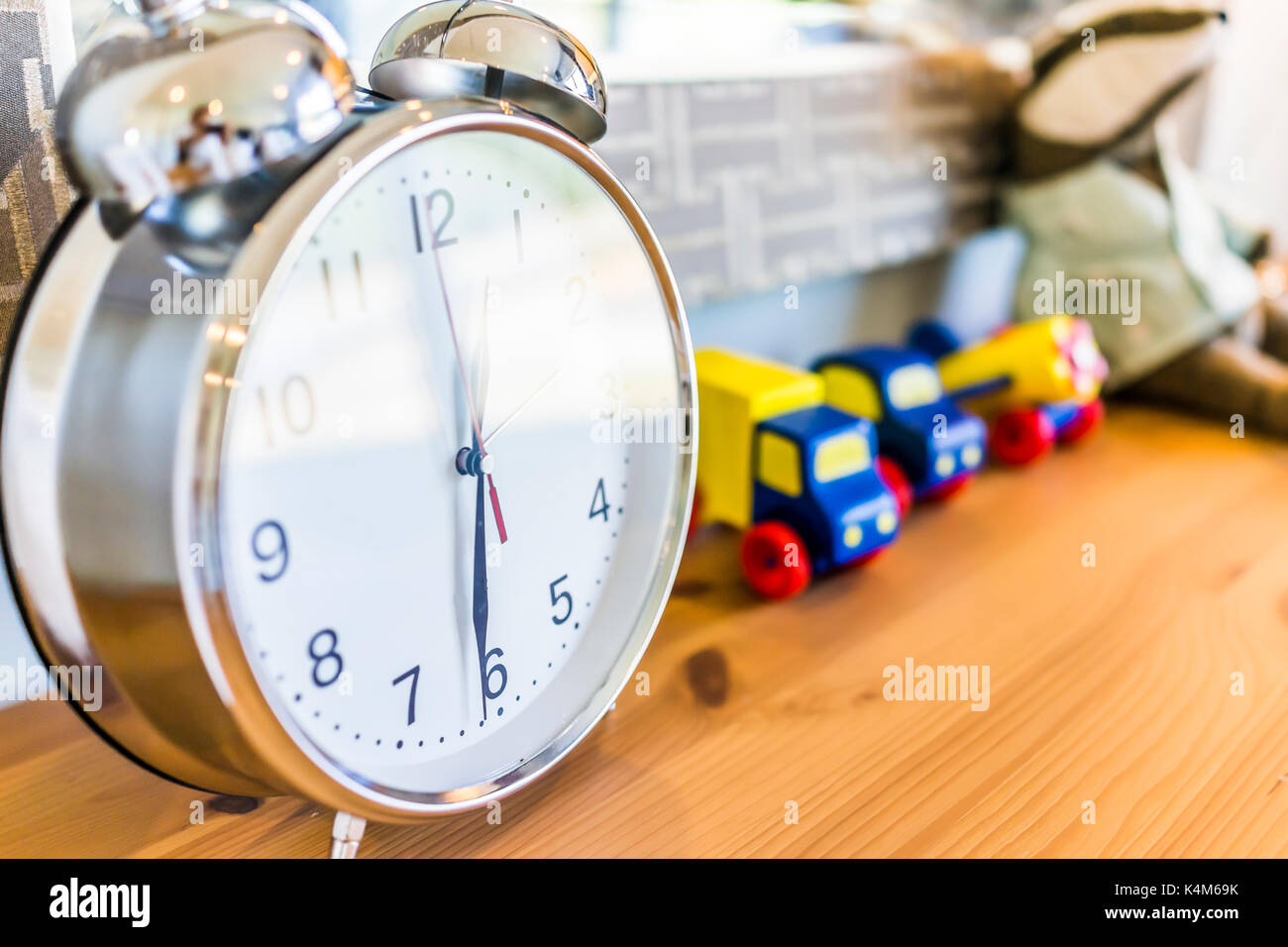 Closeup of modern twin bell ring analogy clock on wooden table desk nightstand with toy trucks in boy's bedroom in model house, home or apartment - Stock Image