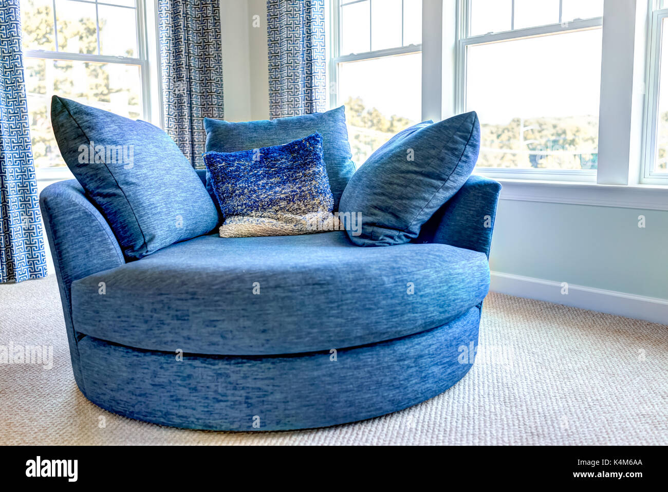 Closeup of new modern blue couch sofa by windows with natural light in home house or apartment