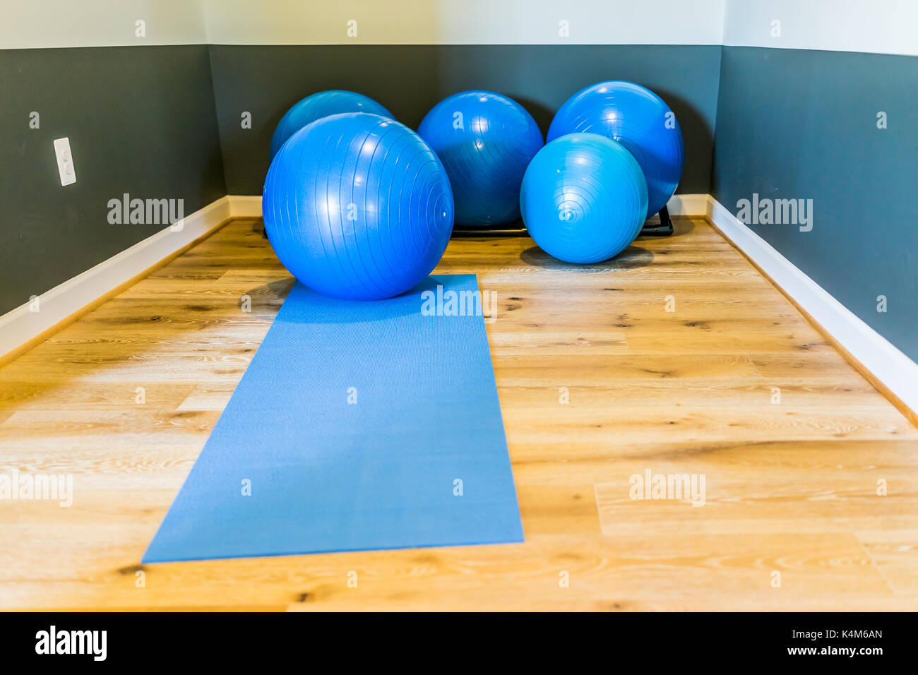 Blue yoga balls in home gym room on wooden floor with mat and nobody