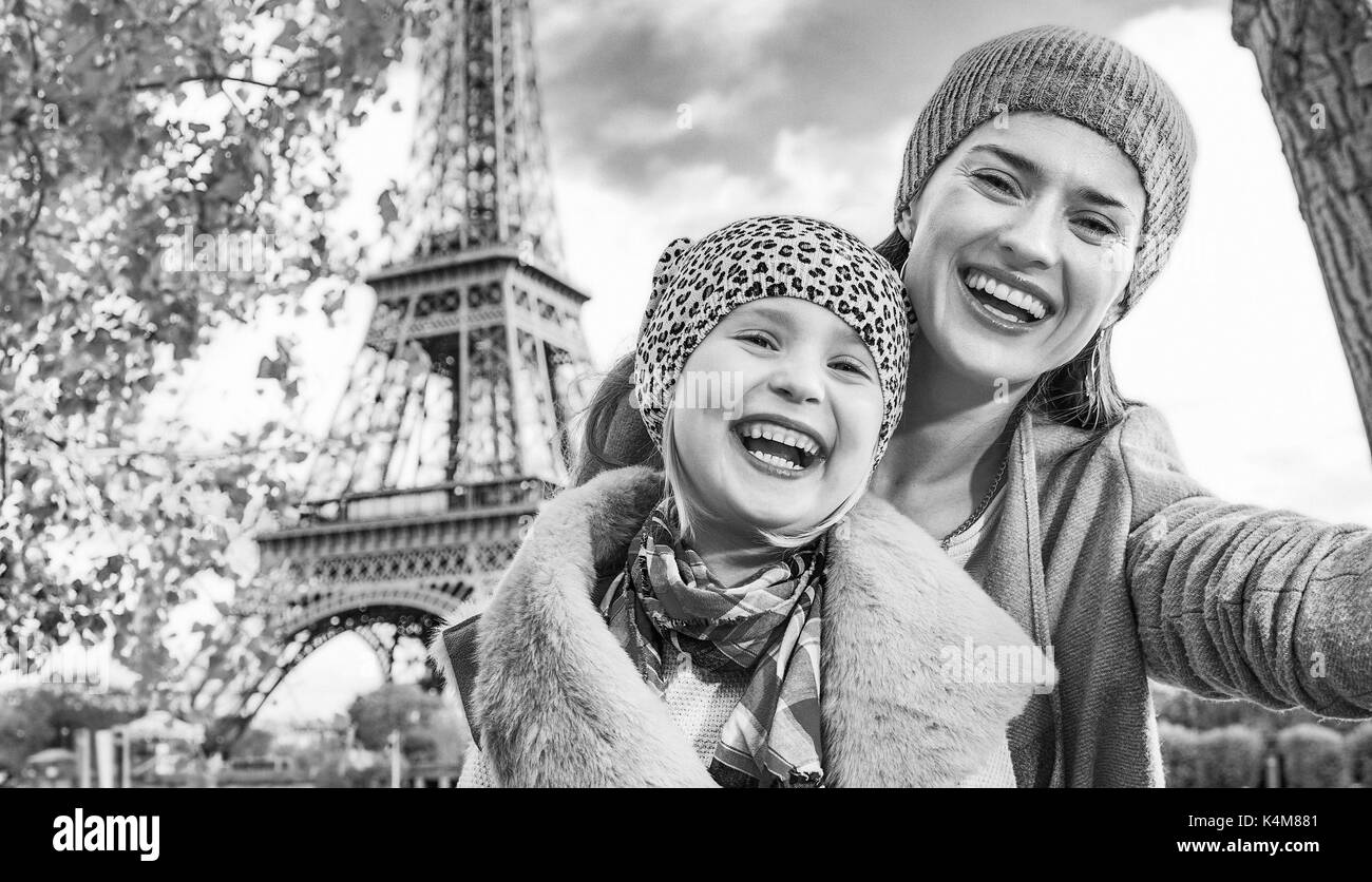 Autumn getaways in Paris with family. happy mother and child travellers on embankment near Eiffel tower in Paris, Stock Photo