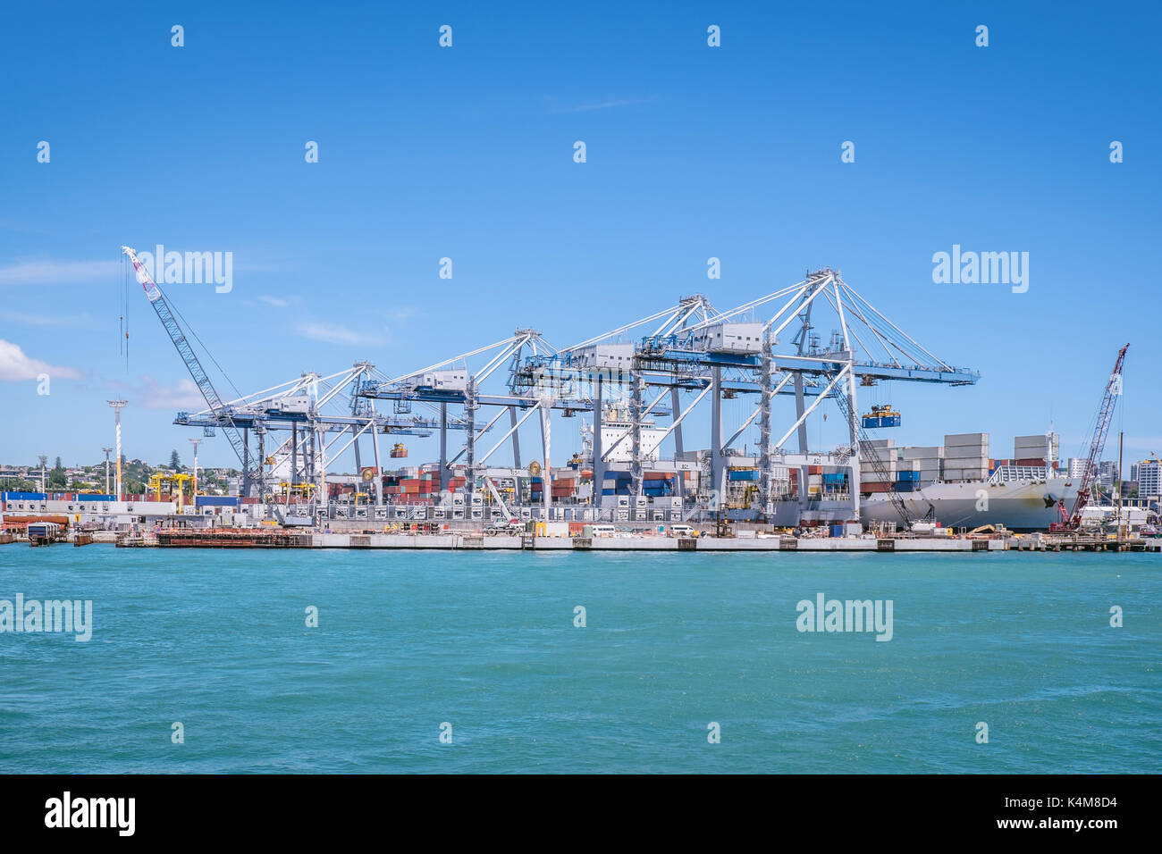 Auckland port with shipping containers, cranes and ship providing transportation for imports and exports in New Zealand, NZ - Stock Image