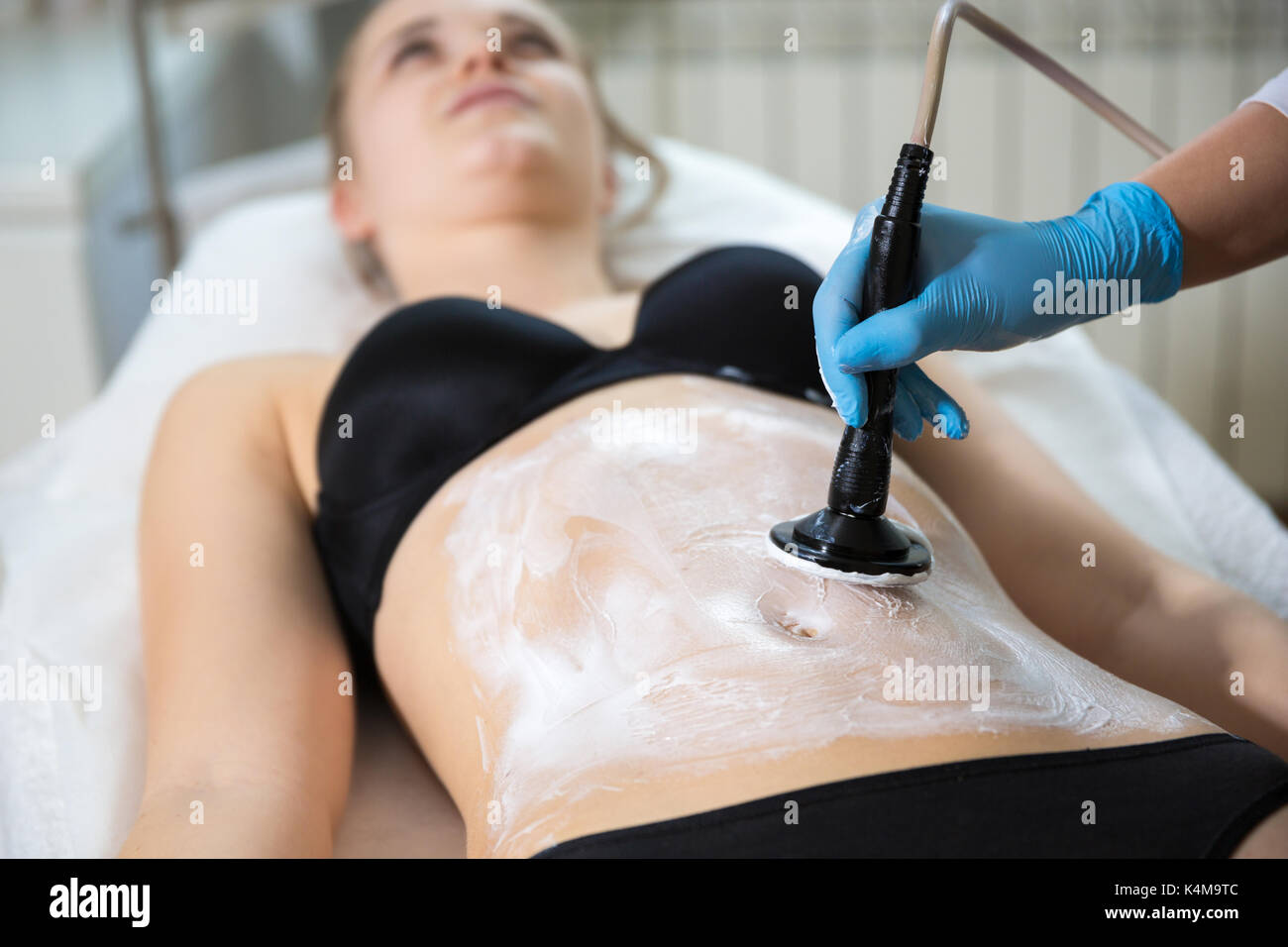 Woman receiving slimming and firming treatment with medical laser - Stock Image