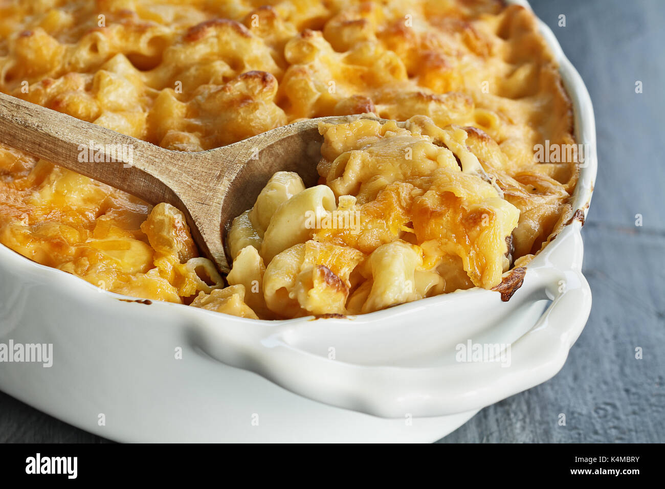 High angel view of a dish of fresh baked macaroni and cheese with a wooden spoon over a rustic dark background. - Stock Image