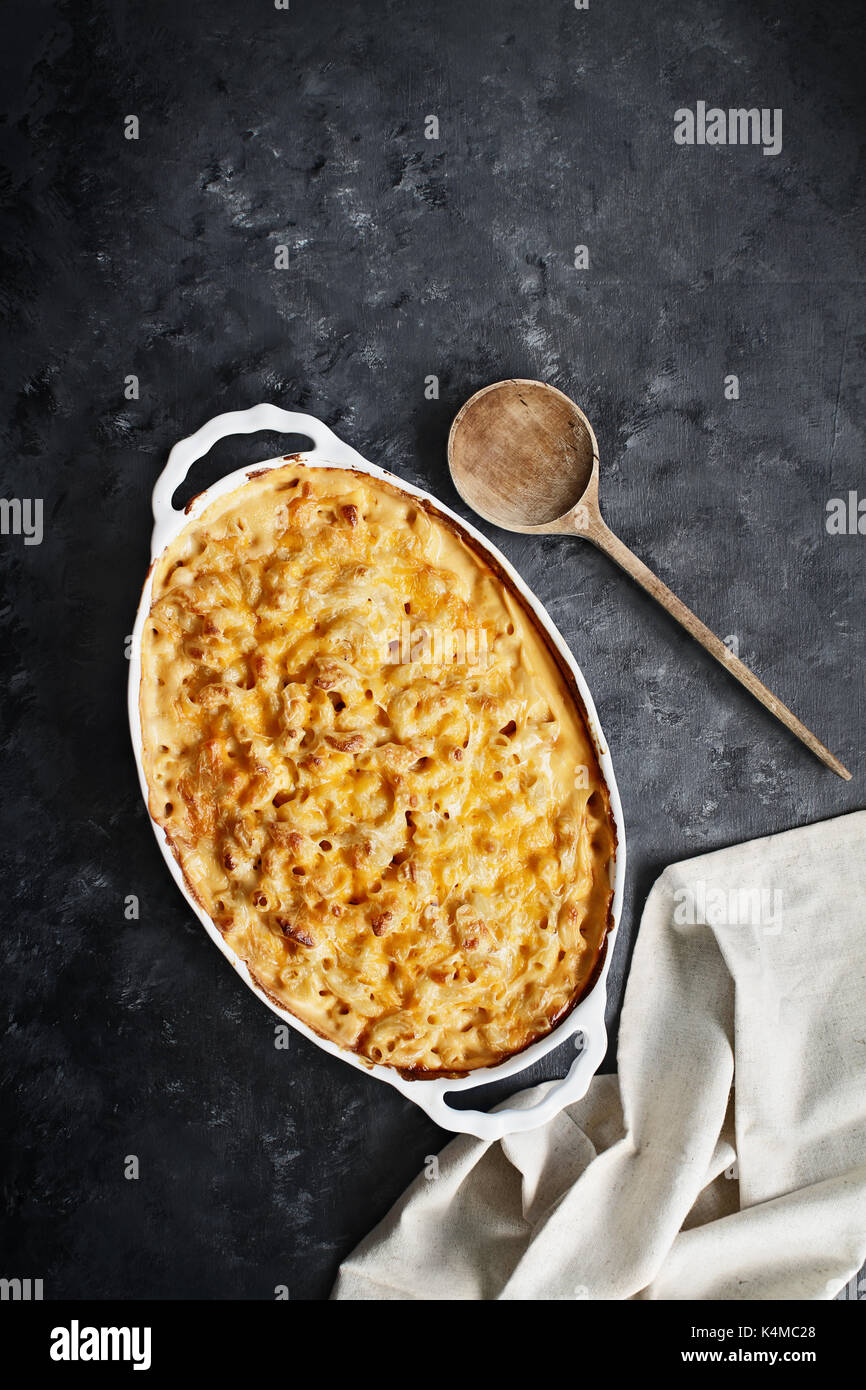 High angel view of a dish of fresh baked macaroni and cheese with table cloth and old wood spoon over a rustic dark background. - Stock Image