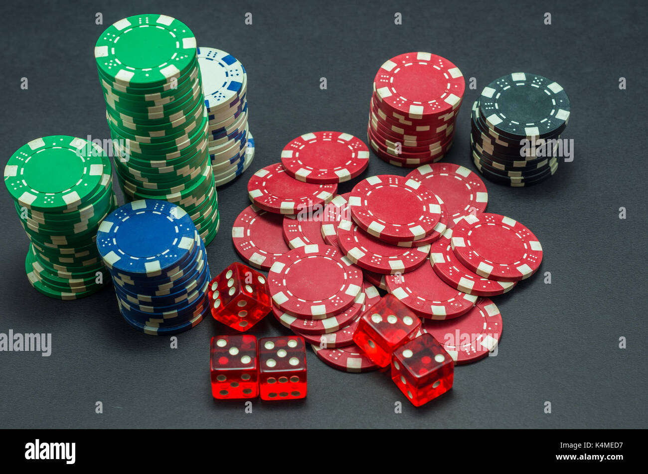 Poker chips stacked on black background and 5 red dice - Stock Image