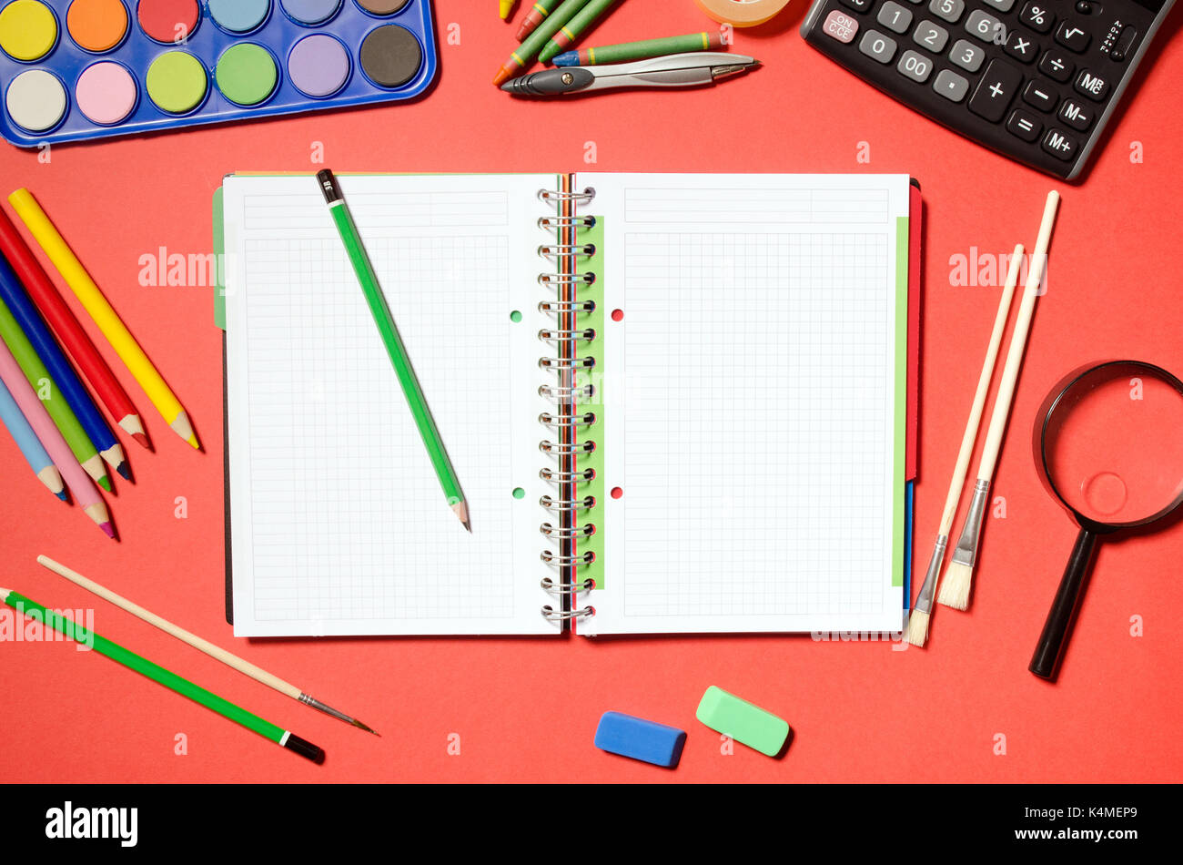 Blank notepad with school and office stationery, red background. stationery office desk top view table school student concept - Stock Image