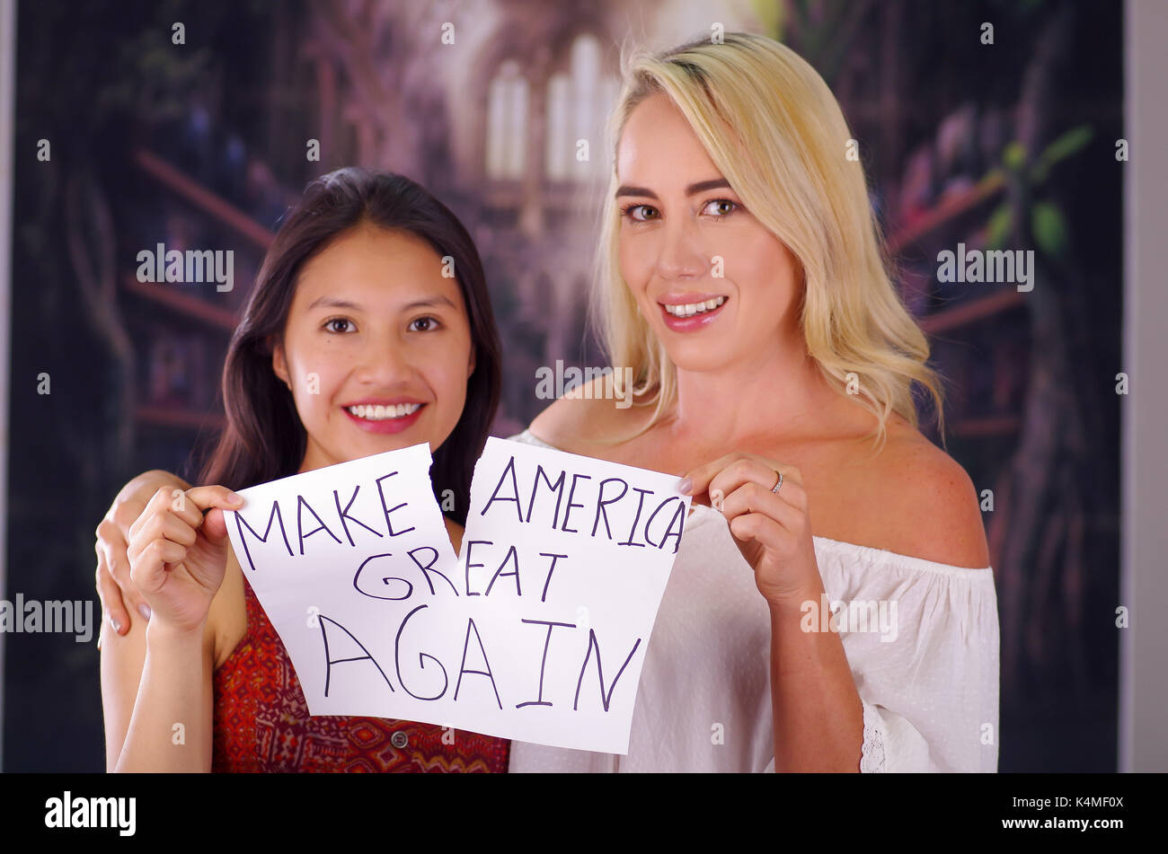 Two young women blonde and latin girl smiling and breaking racism idiosyncrasy from a american person and foreign people, destroying a paper that is written make america great again, racism, violence or discrimination concept - Stock Image
