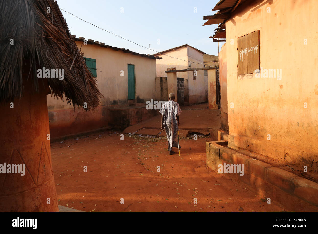Old man walking in Togoville at sunset, Togoville, Togo, West Africa, Africa - Stock Image