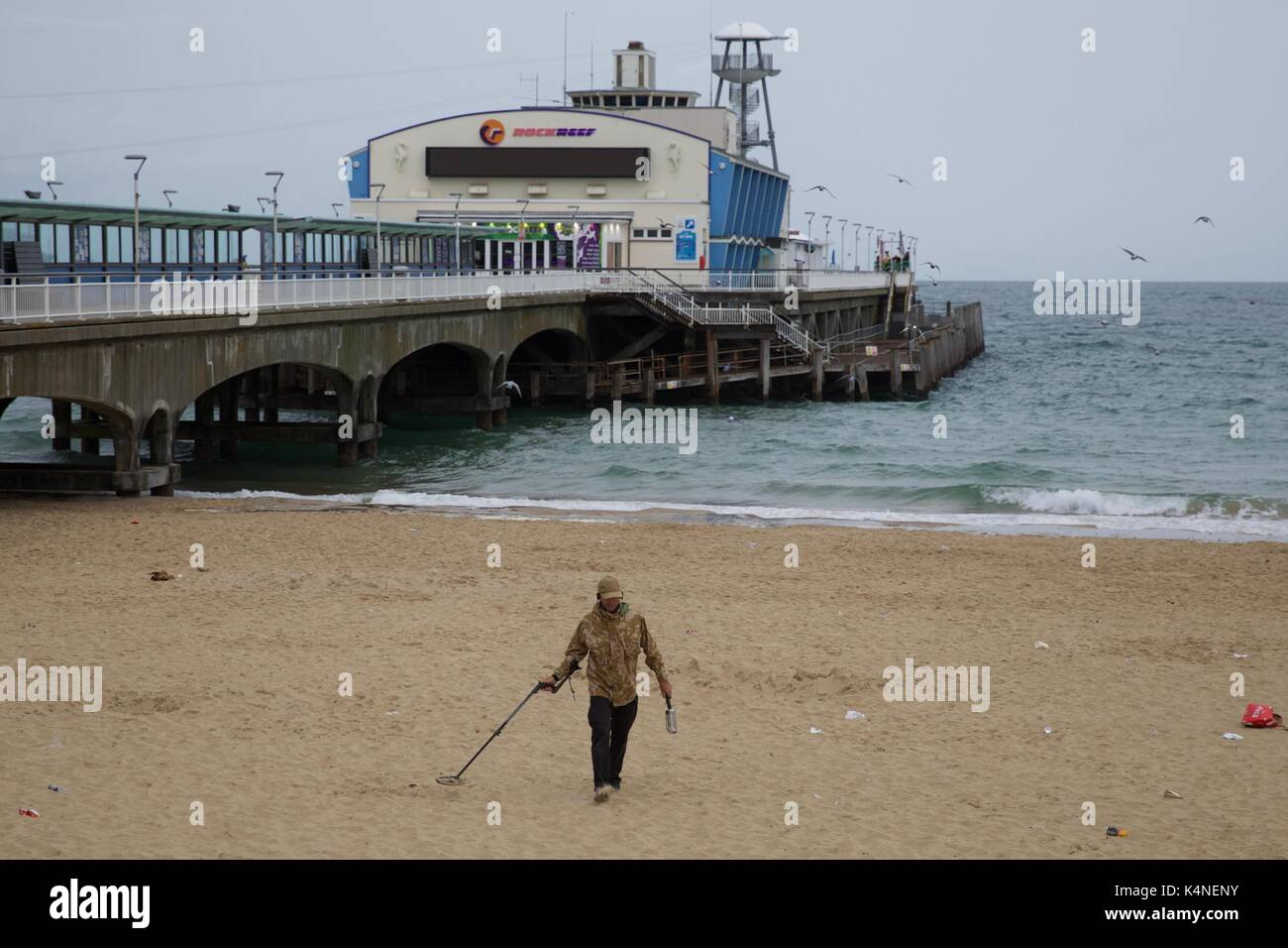 Man using a metal detector on Bournemouth beach with the Bournemouth pier in the background - Stock Image