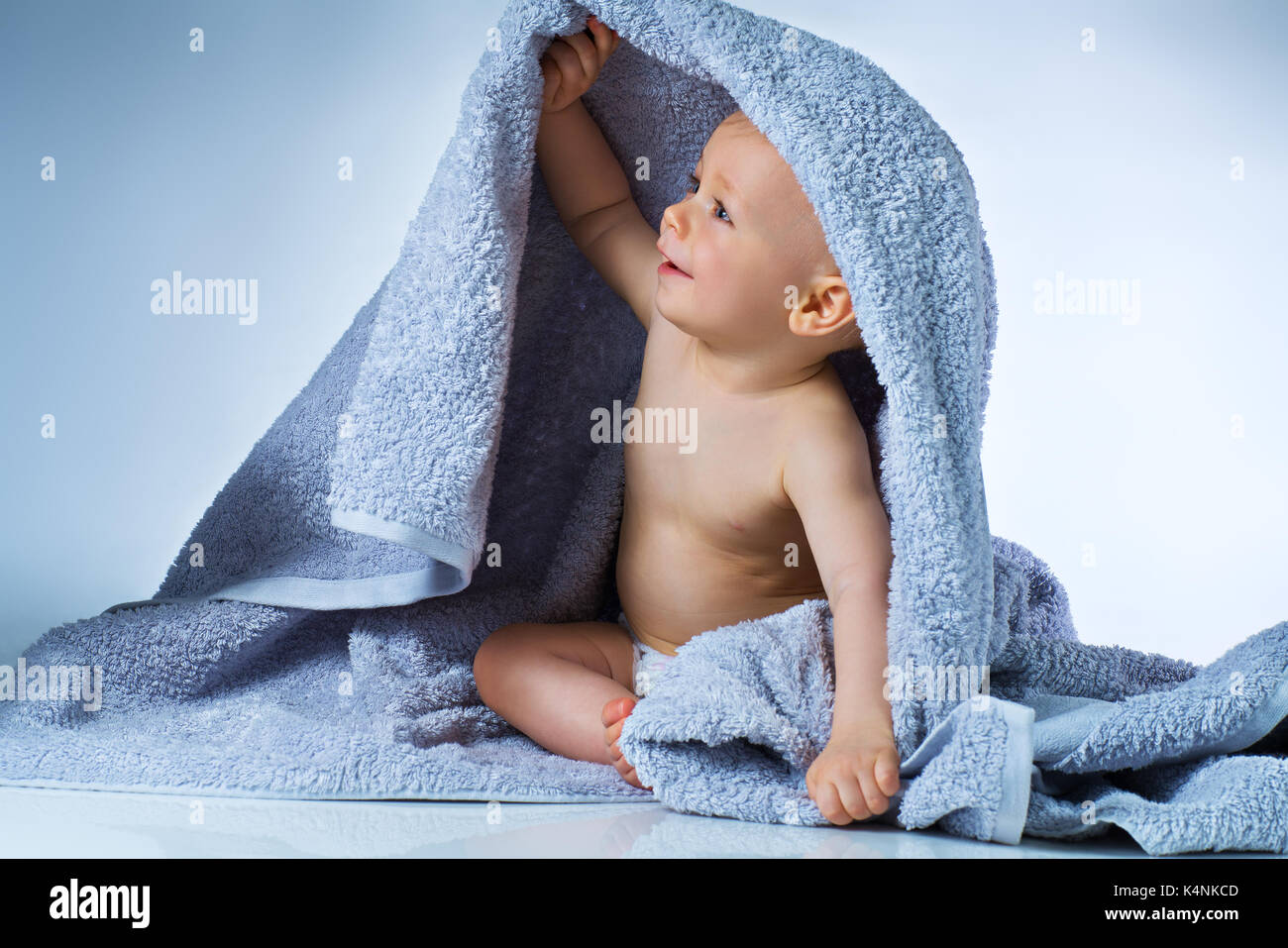 Eight month baby after washing sitting in big soft towel and smiling ...