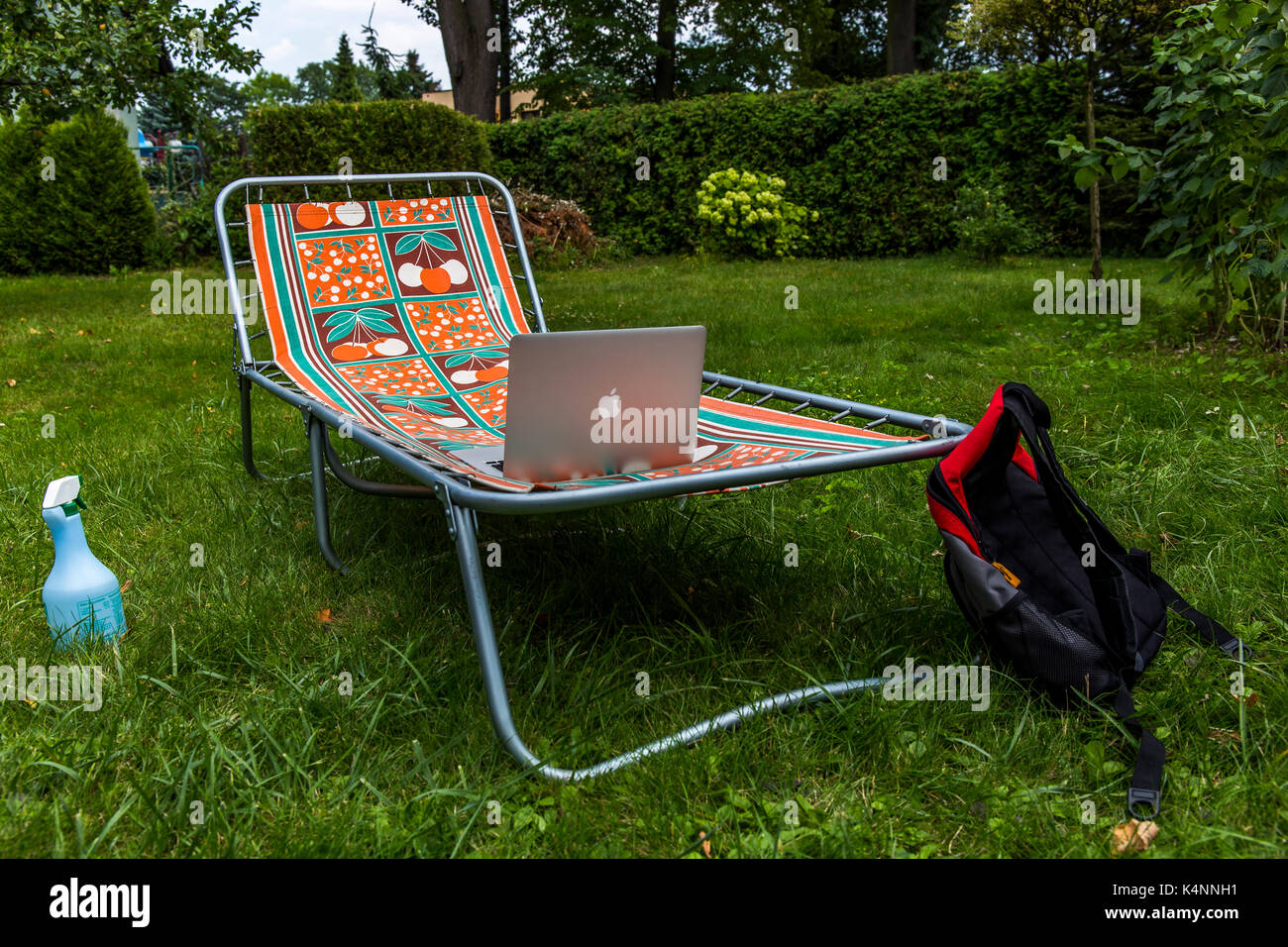Sunbed on the grass with apple macbook on it and a bag. Stock Photo