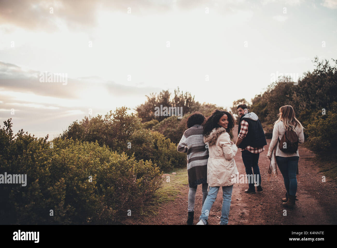 Friends hiking in nature. Group of man and women walking along the countryside road. Woman turning around and looking at camera. - Stock Image