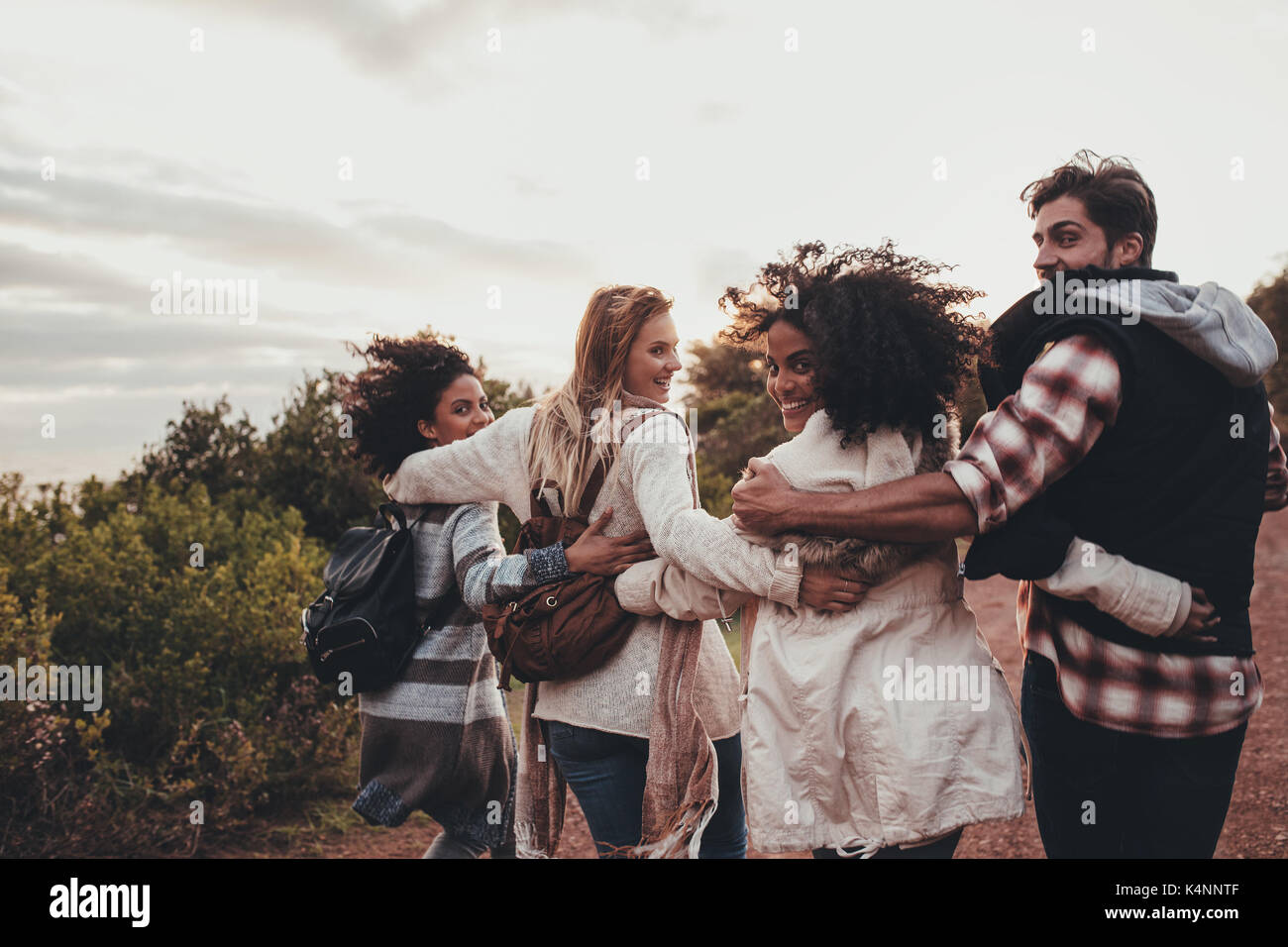 Friends hiking in nature. Group of man and women walking together in countryside. Happy young people turning around and looking at camera. - Stock Image