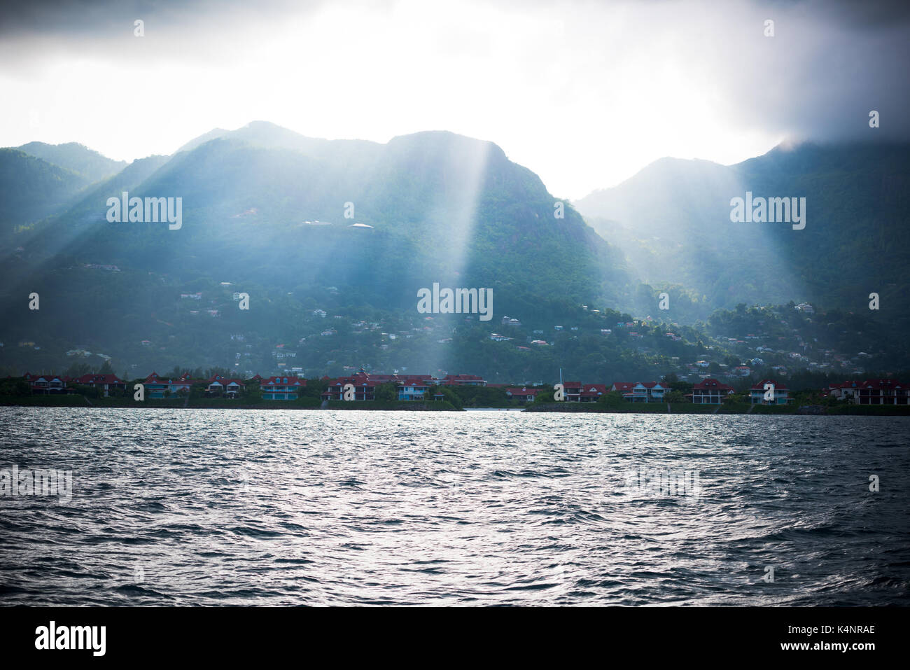 Coastline of Mahe island, Seychelles with sunlight and mountains. View from the boat Stock Photo