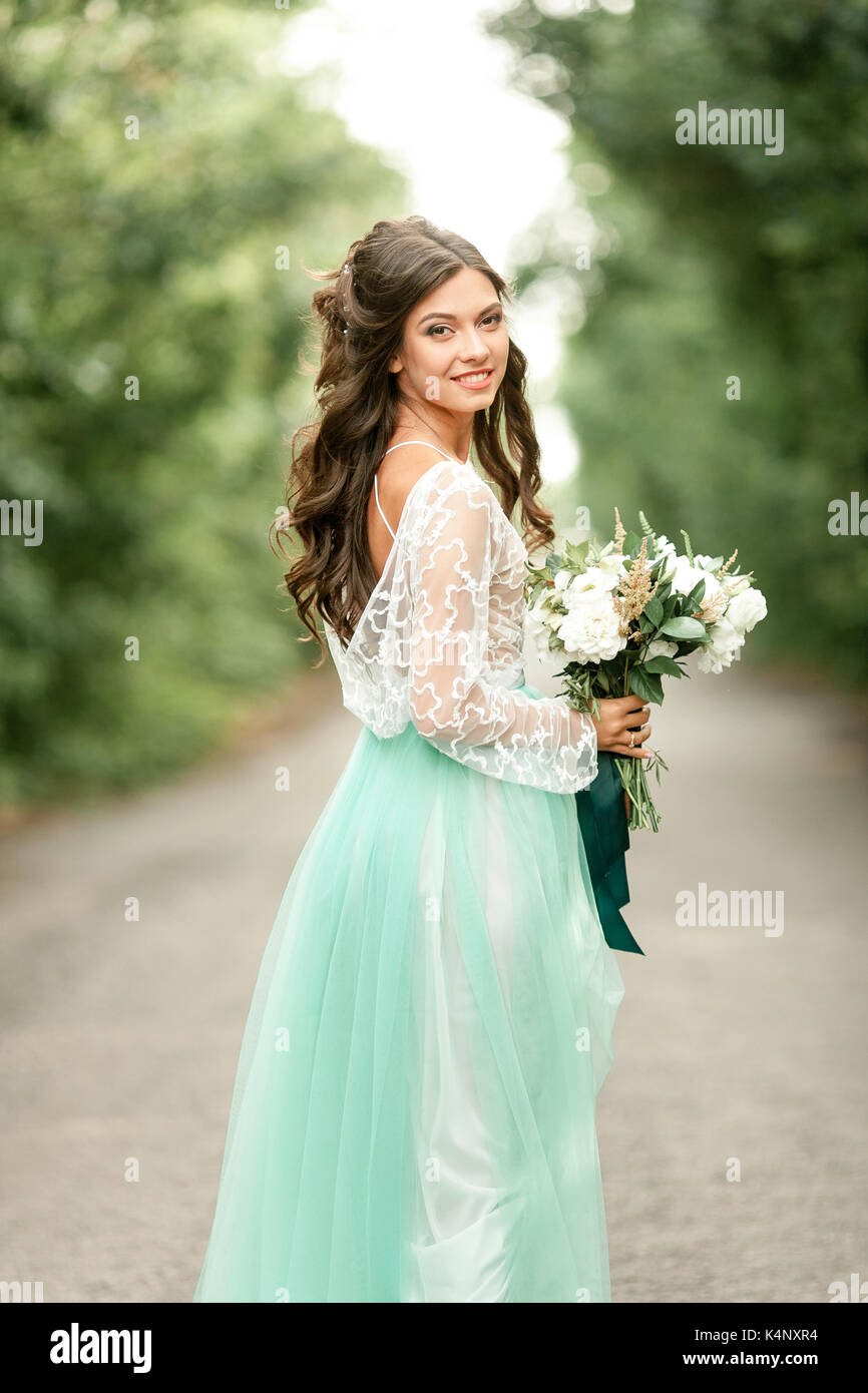 Bride in beautiful wedding dress stands on forest road with bouquet ...