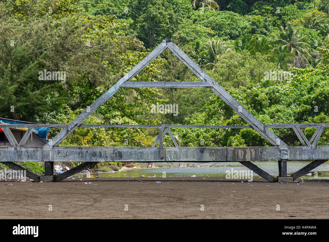 Poorly made concrete foot bridge over dry beach river bed with tropical forest background. - Stock Image