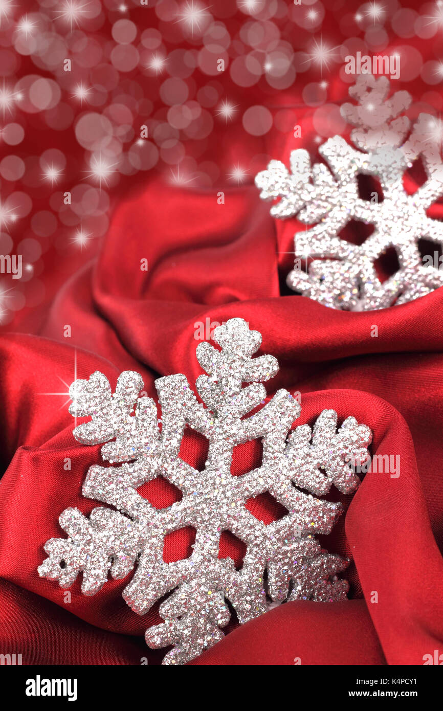 Snowflake on the red satin background - Stock Image