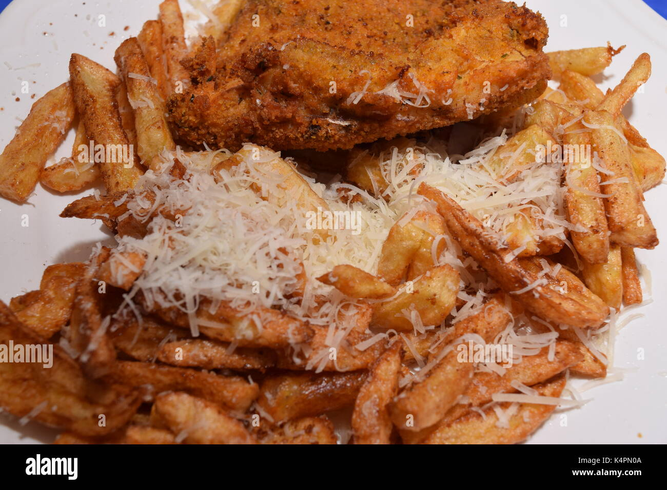 Battered fish and cheesy chips Stock Photo