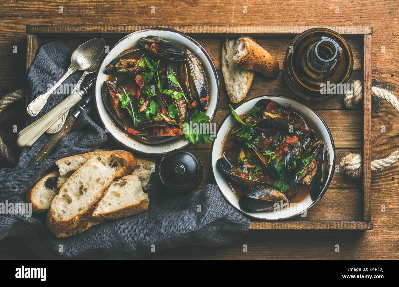 Flat-lay of Belgian boiled mussels in tomato sauce with parsley - Stock Image