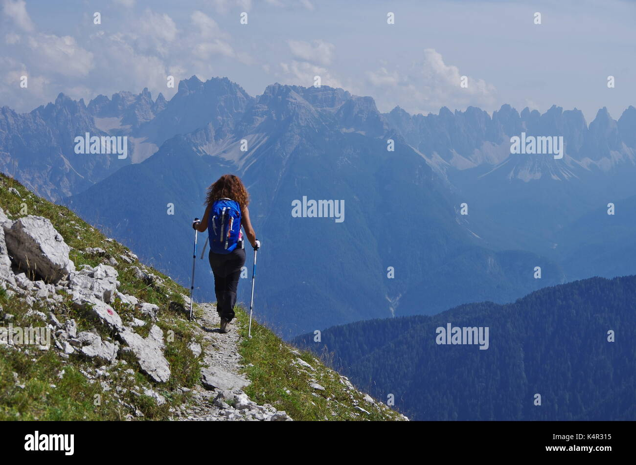 Young femaie trekker hiking on a trail in the Dolomites, Italy, range of Marmarole Stock Photo