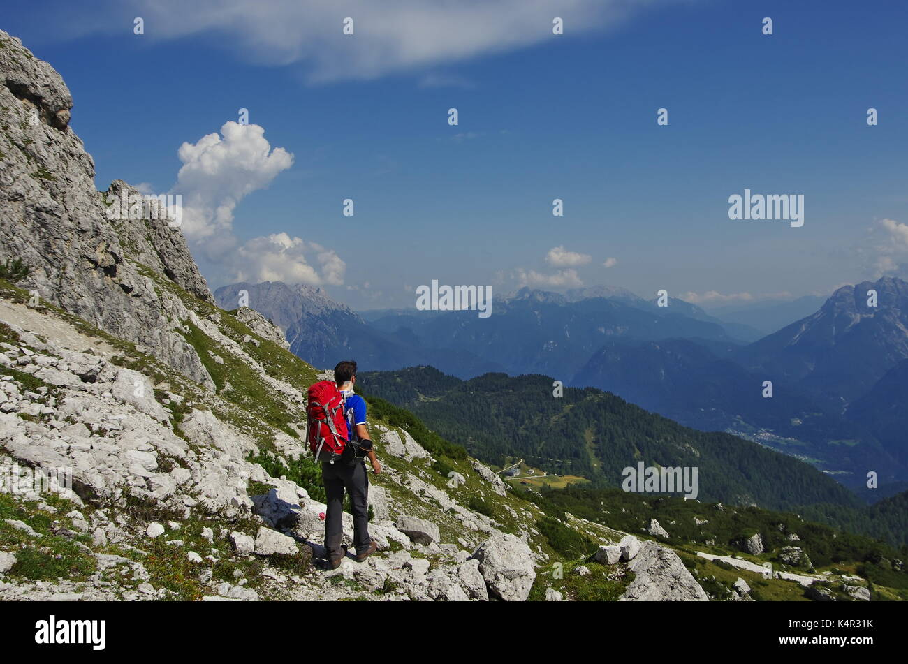 Young maie trekker hiking on a trail in the Dolomites, Italy, range of Marmarole Stock Photo