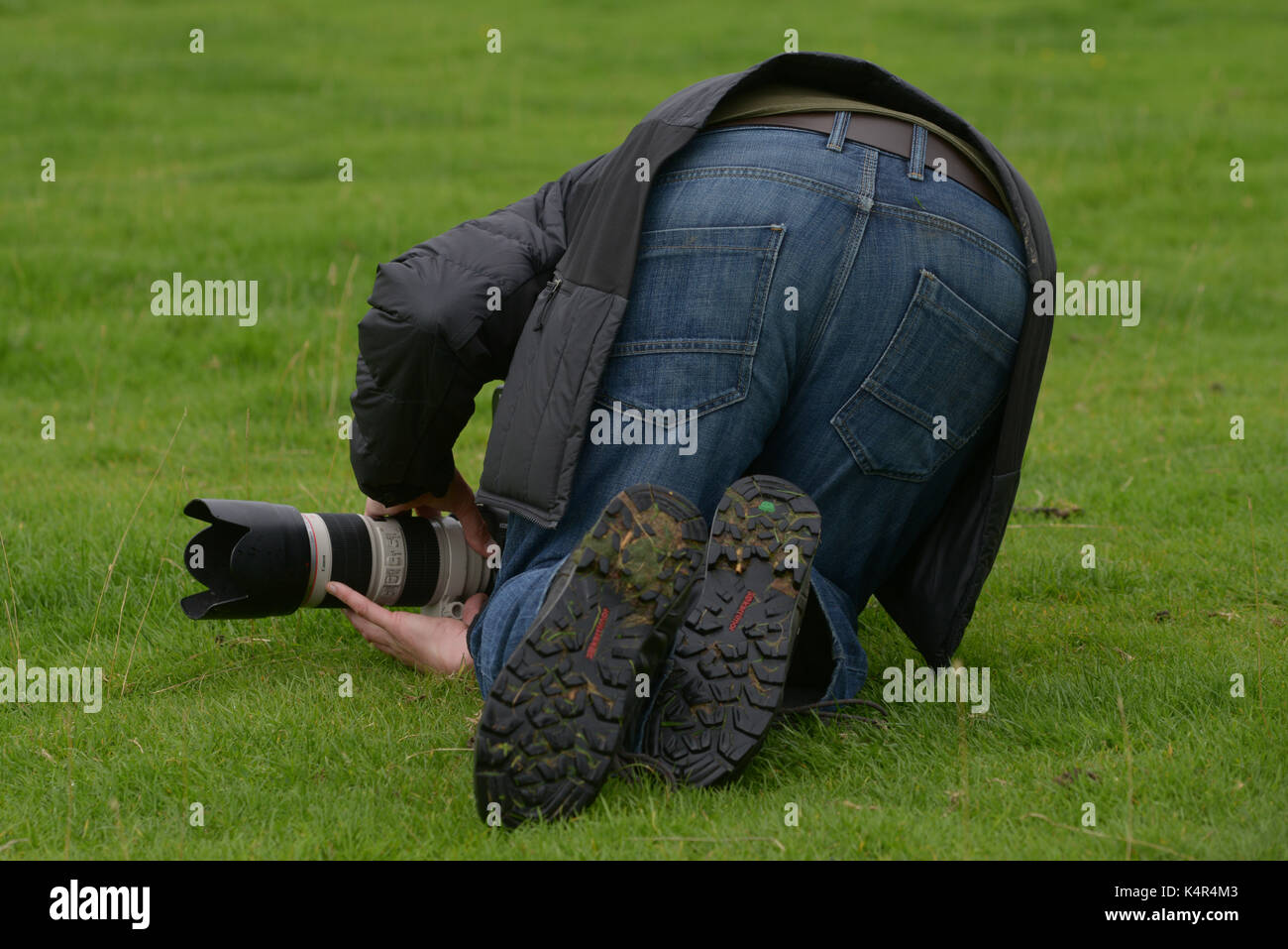 A photographer taking a picture in a strange position. - Stock Image