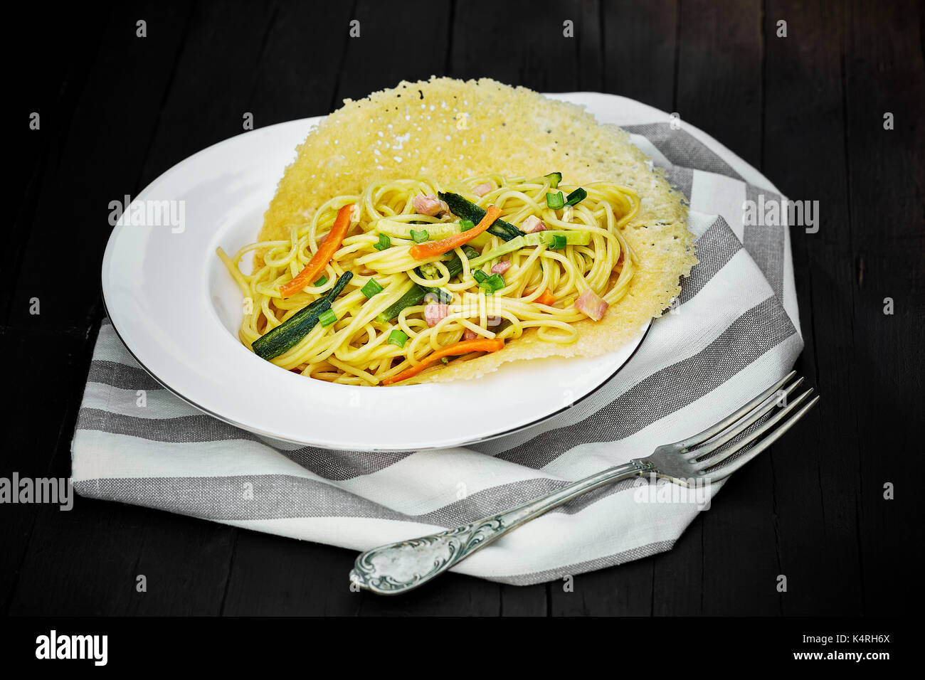 Plate of spaghetti with stuffed vegetables served on melted cheese waffle. - Stock Image