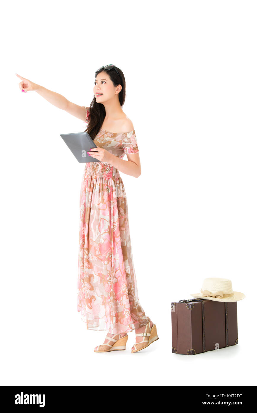 young pretty woman pointing empty area standing on white background with vintage suitcase and wearing summer travel dress clothing holding mobile digi - Stock Image