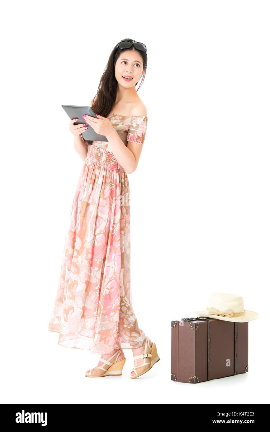 happy beautiful woman traveler looking at empty area thinking travel planning and holding mobile pad computer standing on white background with vintag - Stock Image