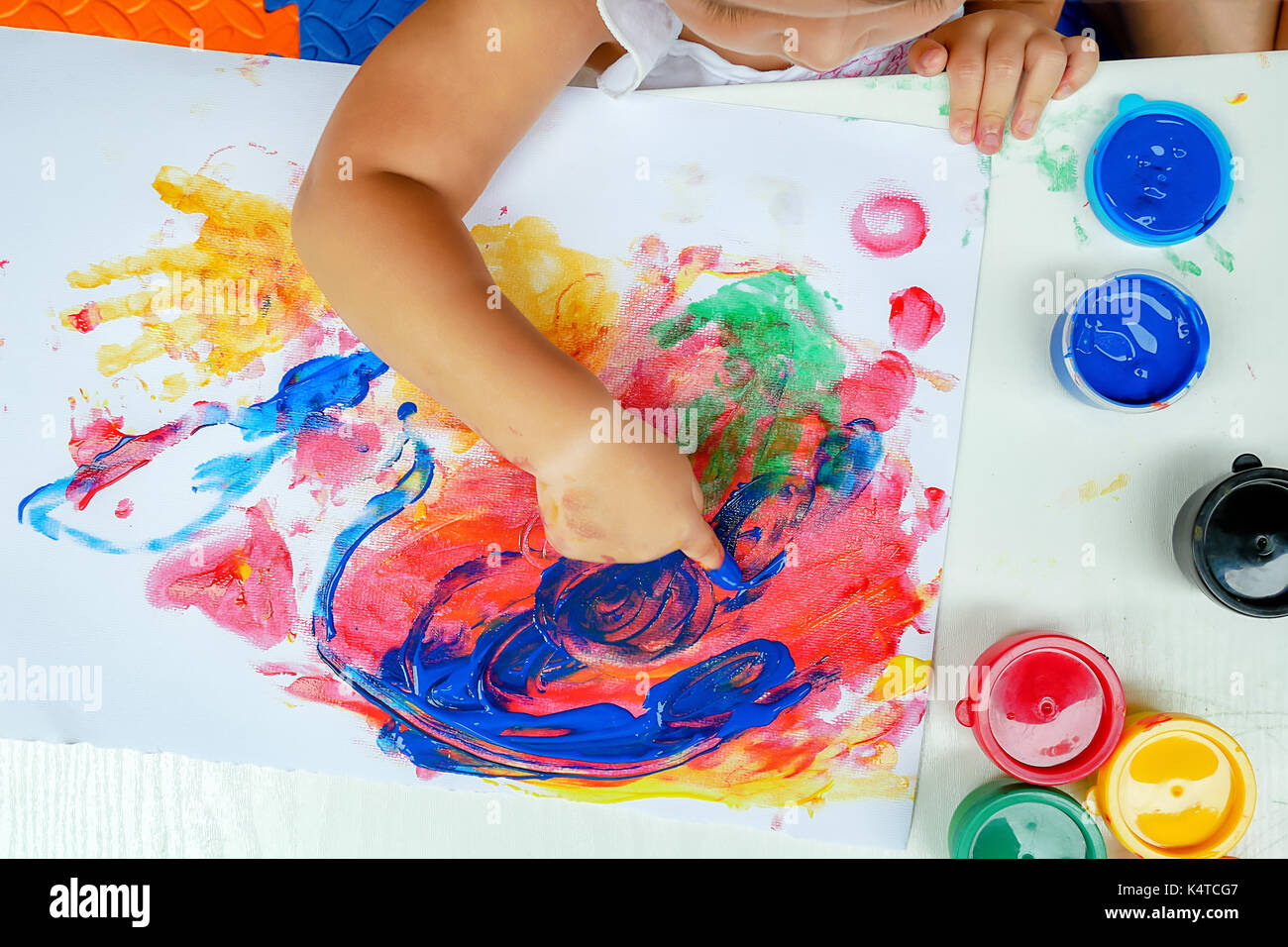 Little girl painting by finger hand paint color ,unlimited