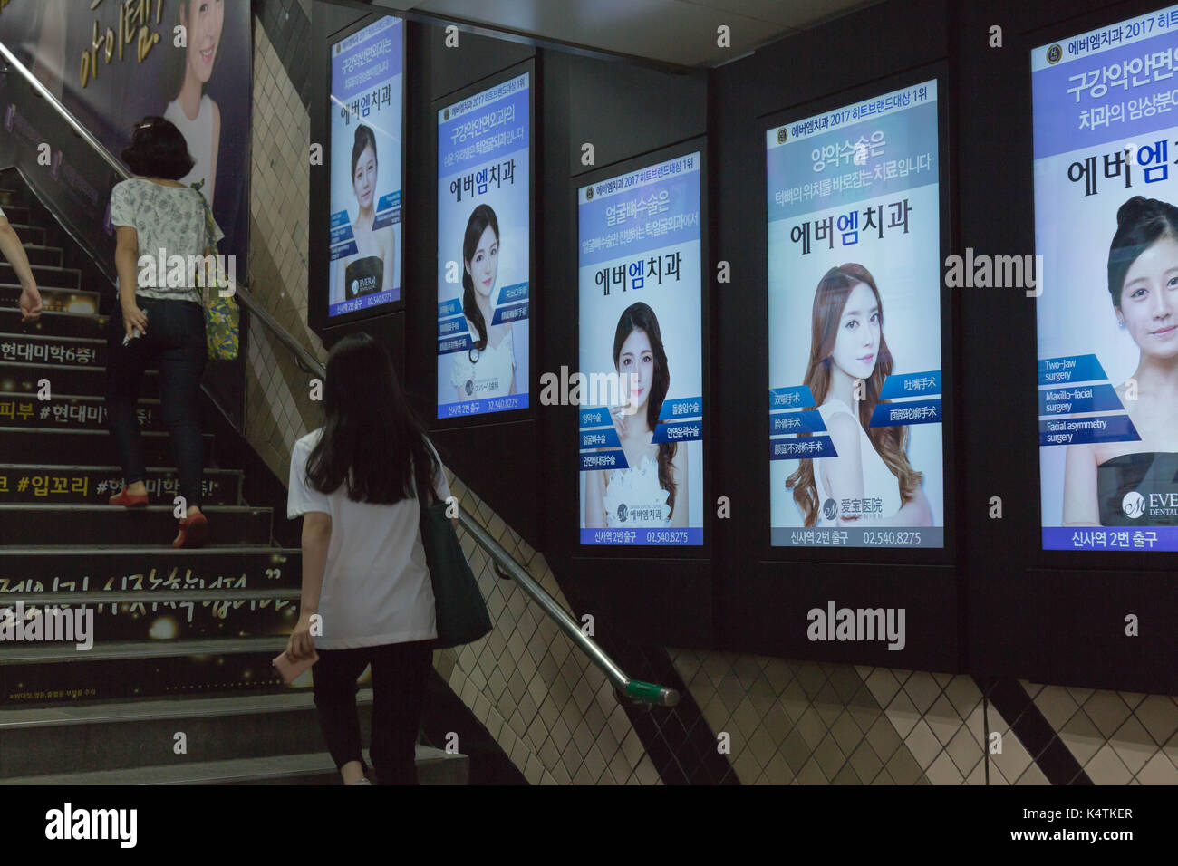 Plastic surgery clinic ads fill the wall and stairs at the subway station of Sinsa in Seoul, South Korea. - Stock Image