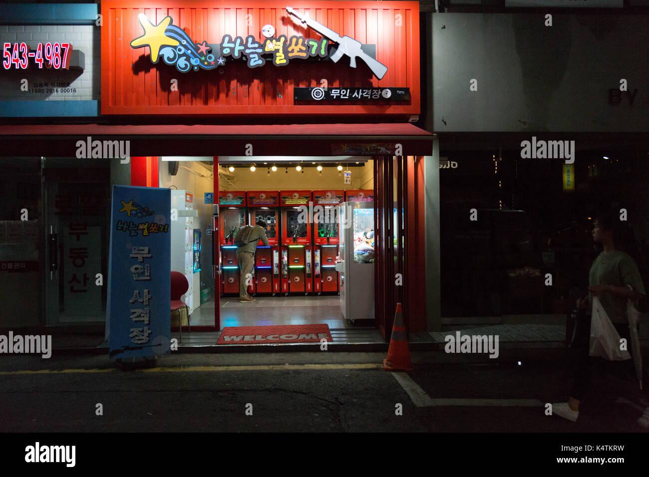 A man plays alone at the arcade shooting range after dark in Sinsa-dog, Gangnum-gu, Seoul, South Korea. - Stock Image