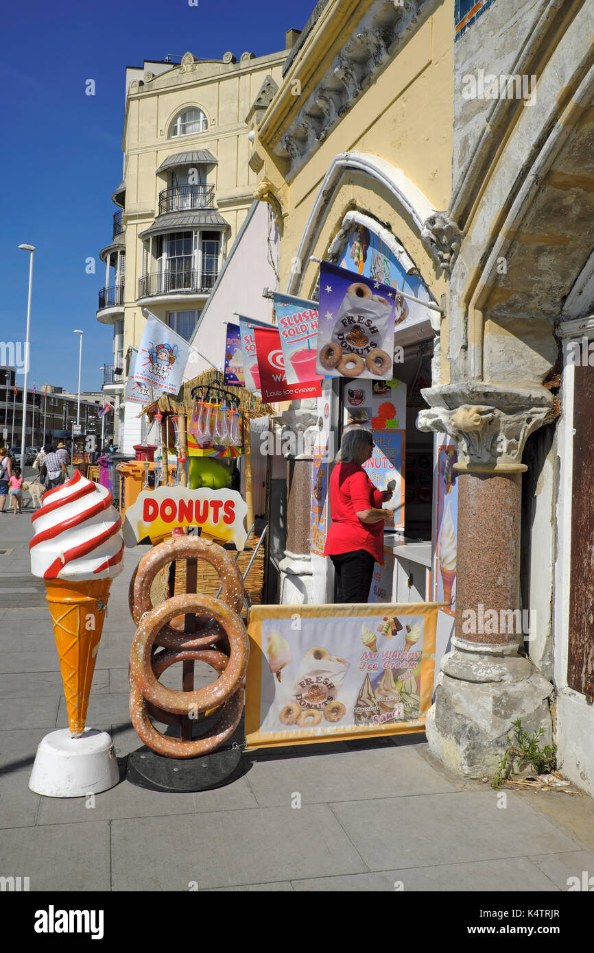 Ice cream and donut shop on the promenade in the seaside resort of Hastings on the seafront at Pelham Place, East Sussex, UK - Stock Image