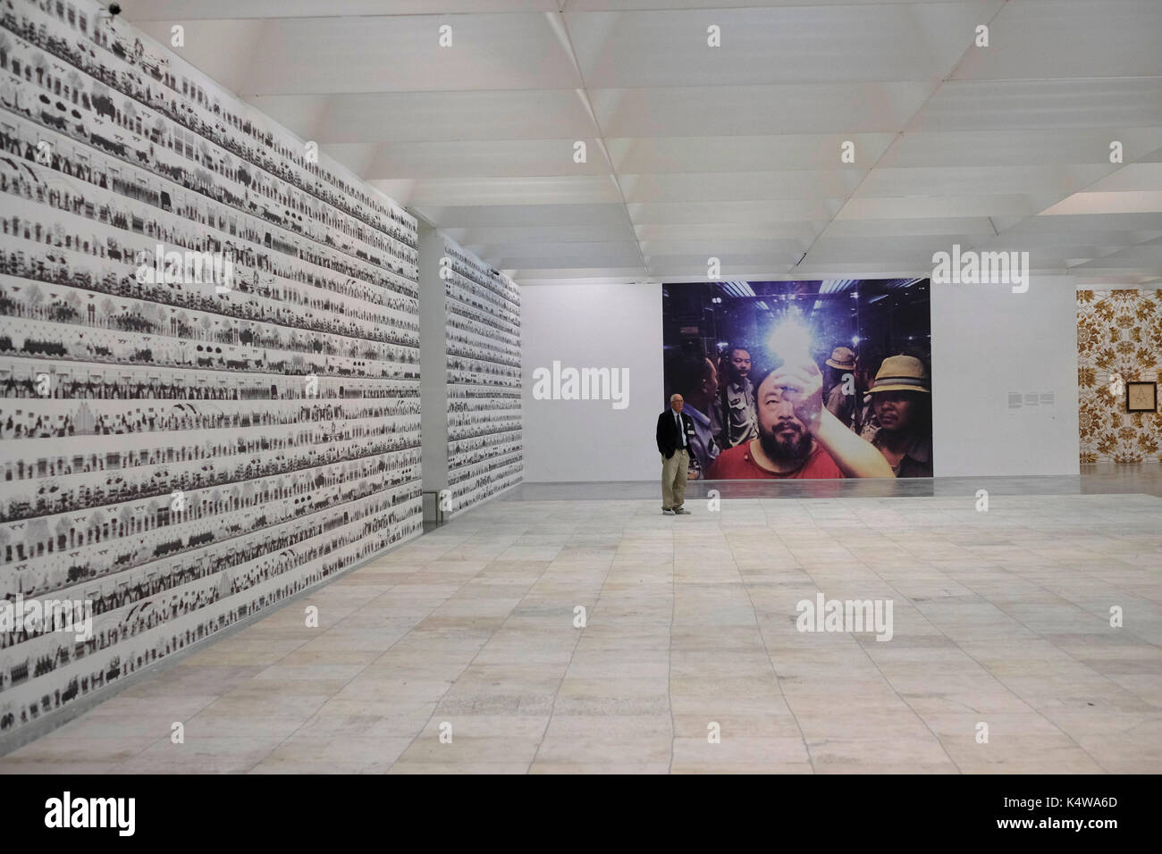 A museum guard stands in the exhibition hall displaying the work of contemporary Chinese artist and activist Ai - Stock Image