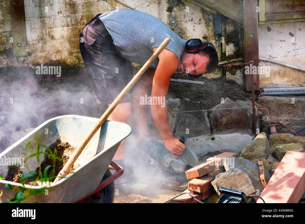 Worker cuts the bricks with a cut-off grinder. - Stock Image