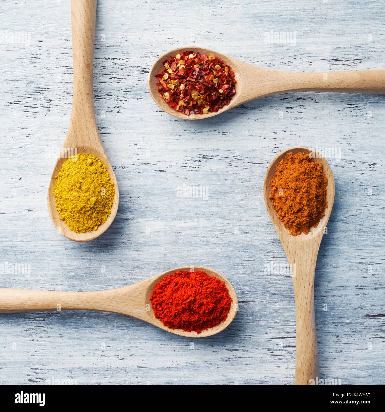 Wooden spoon filled with spices on white painted table - Stock Image
