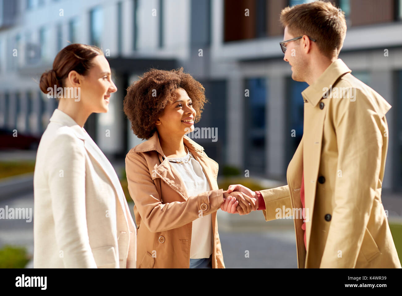happy people shaking hands on city street - Stock Image