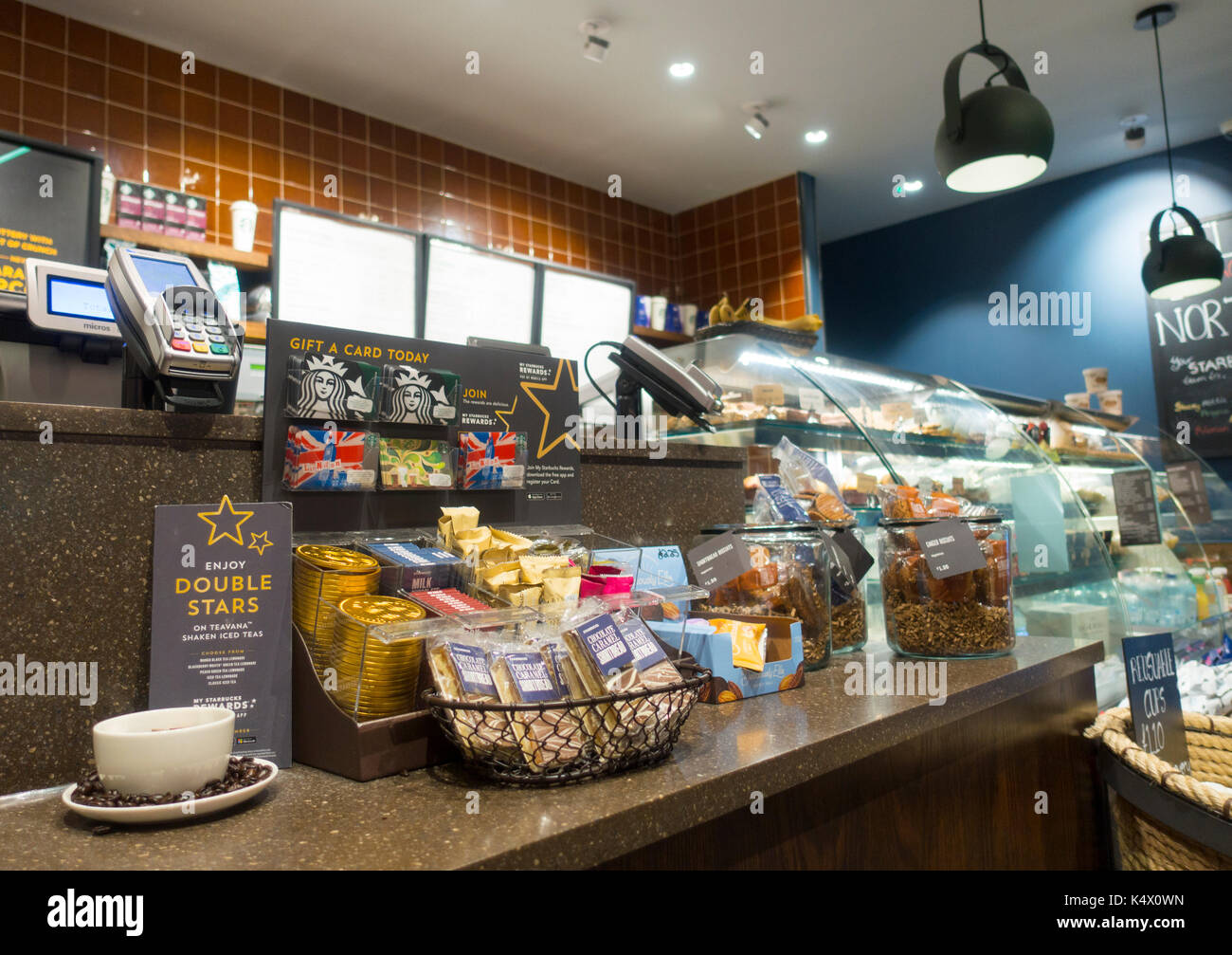 starbucks coffee counter display with products, cake, pastries and