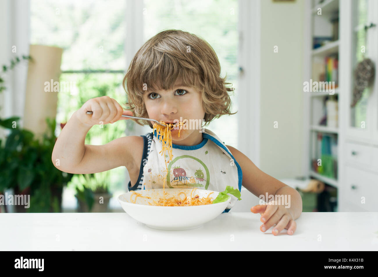 Portrait of a cute young boy making a mess while eating pasta for lunch - Stock Image