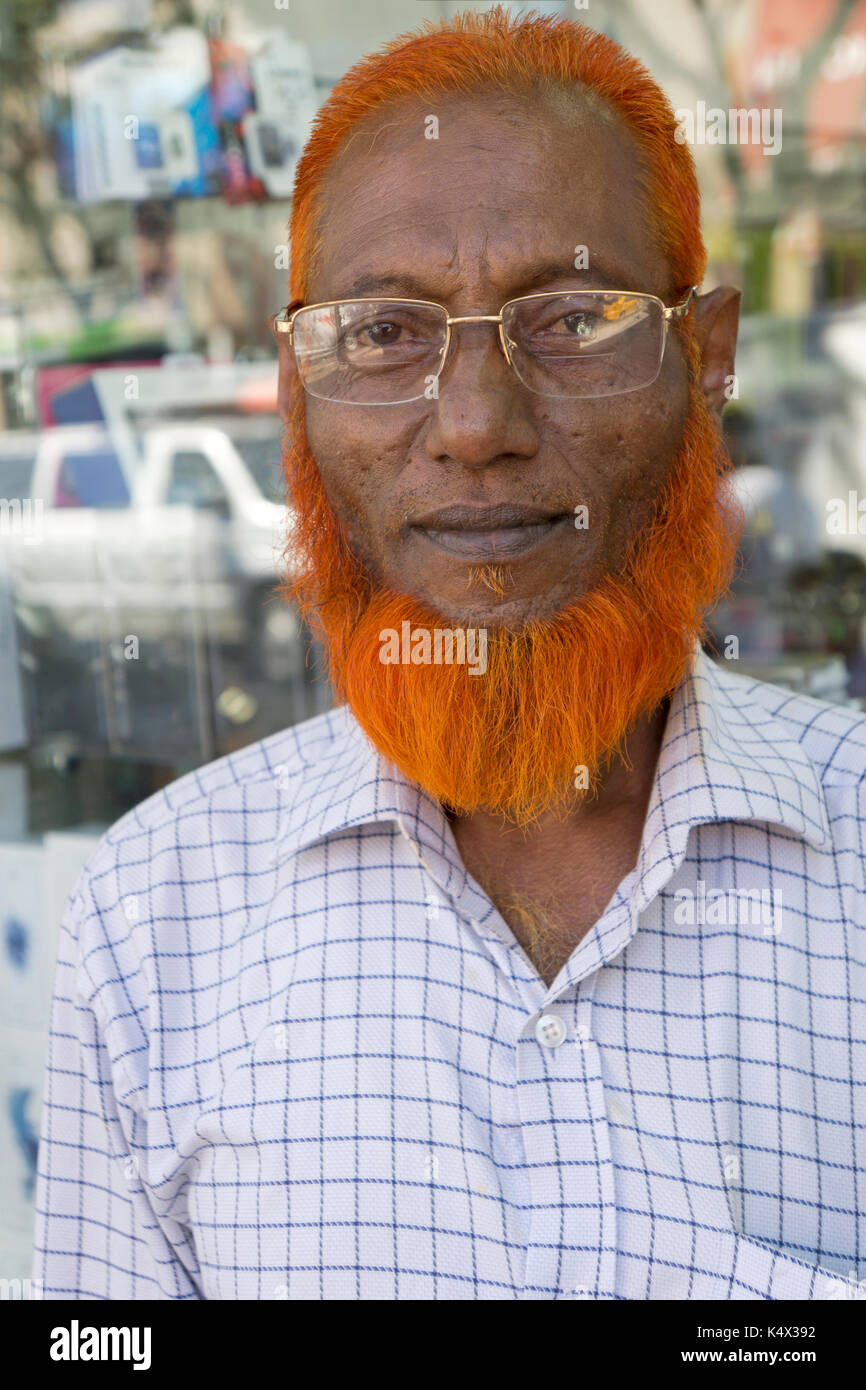 A Bangladeshi man with henna died orange hair and beard on 74th Street in Jackson Heights, Queens, New York City - Stock Image