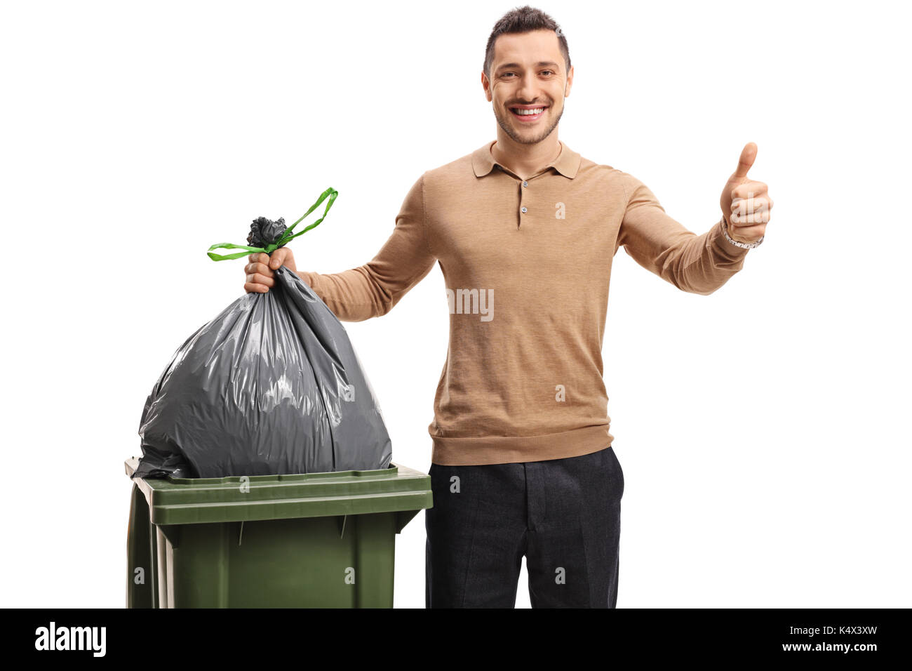 Young man throwing out the trash and making a thumb up gesture isolated on white background - Stock Image