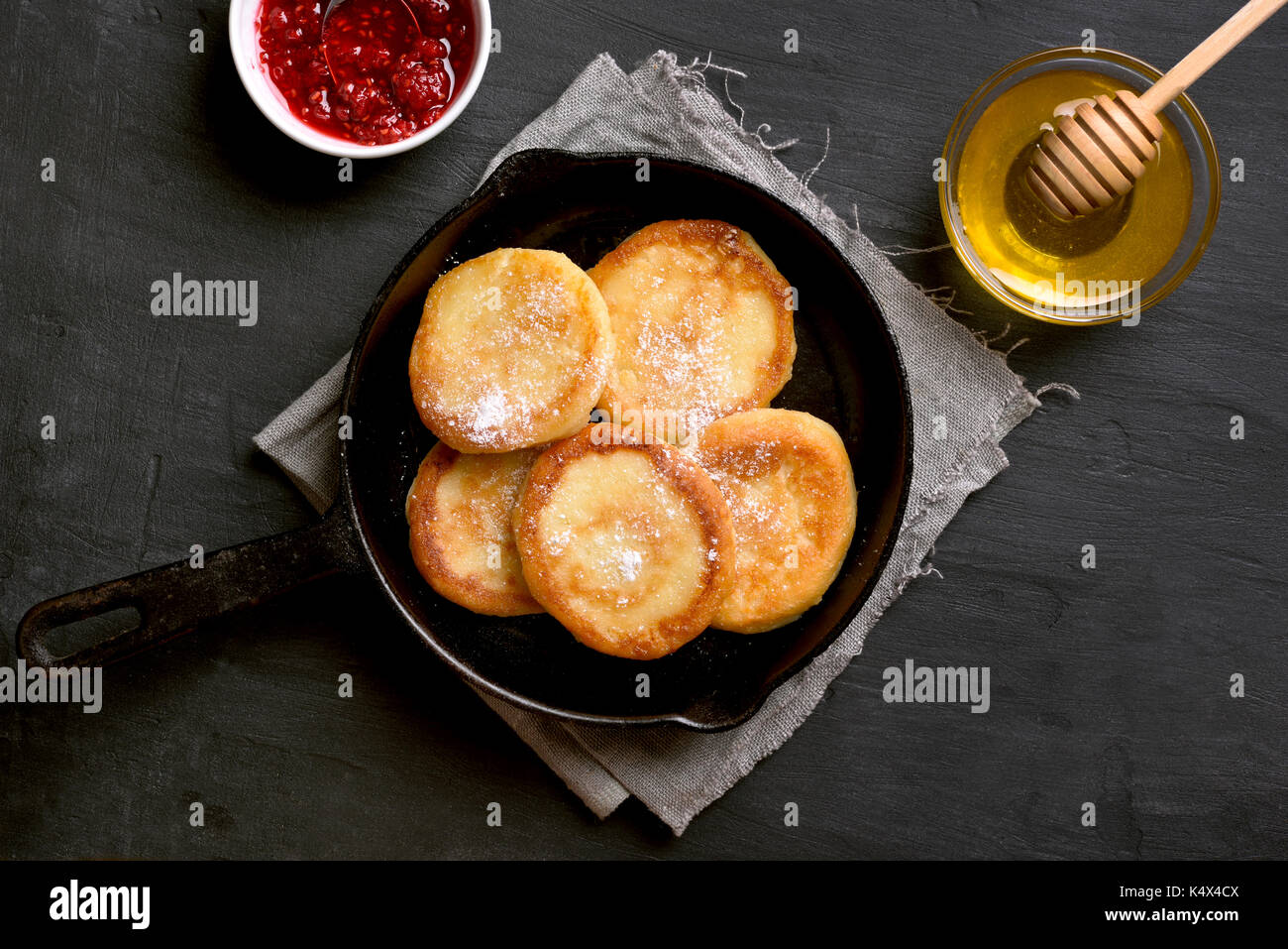 Fritters, curd cheese pancakes in cast iron pan on dark stone background, top view - Stock Image
