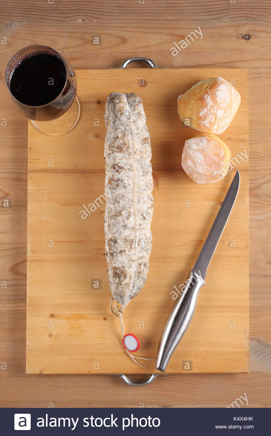 traditional Sant'Olcese salami on a wooden cutting bord - Stock Image