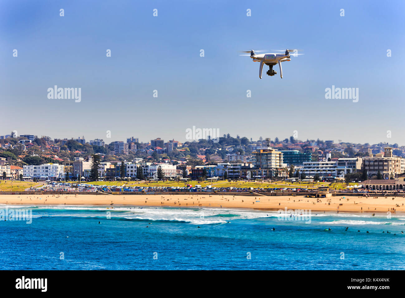 Flying quadrocopter over sand line of famous Australian Bondi beach in Sydney. Active people swimming, surfing and relaxing in iconic tourist destinat - Stock Image